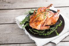 Зажаренный весь цыпленок с травами над естественной деревянной предпосылкой кто стоковые изображения rf