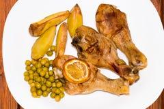 Зажаренный в духовке drumstick цыпленк цыпленка с картошками и зелеными горохами на плите Стоковое Изображение RF