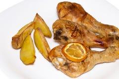 Зажаренный в духовке drumstick цыпленк цыпленка с картошками на плите над деревянным bac Стоковое Фото