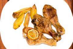 Зажаренный в духовке drumstick цыпленк цыпленка с картошками на плите над деревянным bac Стоковая Фотография