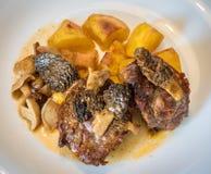 Зажаренный в духовке свинина с грибами и картошками на белой плите Стоковое фото RF