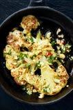 Зажаренный в духовке стейк цветной капусты с погружением добавлению с арахисами, chili и свежей петрушкой на железной сковороде Стоковое Изображение