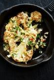 Зажаренный в духовке стейк цветной капусты с погружением добавлению с арахисами, chili и свежей петрушкой на железной сковороде Стоковые Изображения