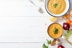 Зажаренный в духовке суп тыквы и моркови на белой деревянной предпосылке скопируйте космос Вегетарианская принципиальная схема Стоковые Изображения RF