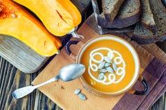 Зажаренный в духовке суп тыквы с сливк, свежими тыквами и семенами тыквы в плите на деревянной предпосылке скопируйте космос Стоковые Изображения RF