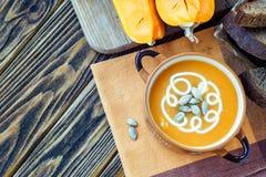 Зажаренный в духовке суп тыквы с сливк, свежими тыквами и семенами тыквы в плите на деревянной предпосылке скопируйте космос Стоковые Изображения