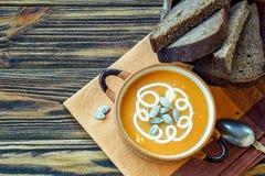 Зажаренный в духовке суп тыквы с сливк, свежими тыквами и семенами тыквы в плите на деревянной предпосылке скопируйте космос Стоковое Фото