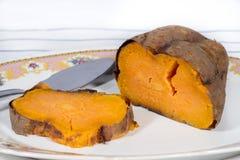 Зажаренный в духовке сладкий картофель в керамическом подносе с флористическим украшением Стоковые Изображения RF