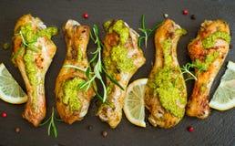 Зажаренный в духовке drumstick цыпленк цыпленка в зеленом соусе с лимоном на черном b Стоковое фото RF