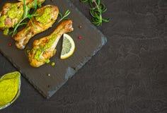 Зажаренный в духовке drumstick цыпленк цыпленка в зеленом соусе с лимоном на черном b Стоковая Фотография