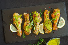 Зажаренный в духовке drumstick цыпленк цыпленка в зеленом соусе с лимоном на черном b Стоковое Изображение