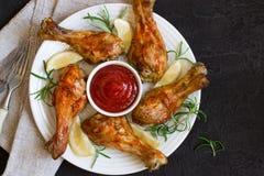 Зажаренный в духовке drumstick цыпленк цыпленка в красном базилике соуса и лимон на blac Стоковое фото RF