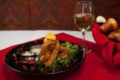 Зажаренный обедающий ресторана для гурманов calamari полный с белым вином и хлебом стоковое изображение rf