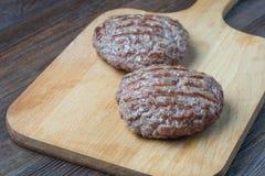 2 зажаренный пирожок гамбургера на разделочной доске Стоковое Изображение RF