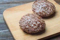 2 зажаренный пирожок гамбургера на разделочной доске Стоковая Фотография