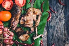 Зажаренный свинина на лист банана с томатом, chili и луком на древесине Стоковое Изображение