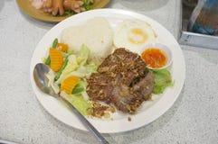 Зажаренный свинина с чесноком, перцем и яичницей на рисе еда тайская Стоковые Изображения