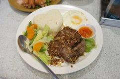 Зажаренный свинина с чесноком, перцем и яичницей на рисе еда тайская Стоковое Изображение RF