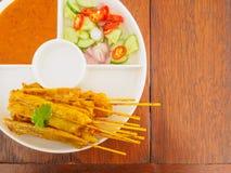 Зажаренный свинина Satay с соусом и уксусом арахиса на деревянном столе Стоковые Изображения