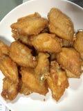 Зажаренный средний цыпленок крыла на белой плите Стоковые Изображения