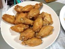 Зажаренный средний цыпленок крыла на белой плите Стоковая Фотография