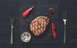 Зажаренный стейк говядины на темной предпосылке деревянного стола, взгляд сверху Стоковая Фотография