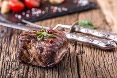 Зажаренный стейк говядины с розмариновым маслом, солью и перцем на старой разделочной доске bedroll стоковое изображение