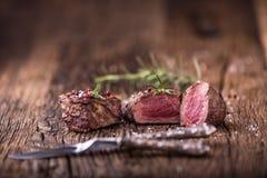 Зажаренный стейк говядины с розмариновым маслом, солью и перцем на старой разделочной доске bedroll стоковое фото rf