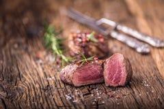 Зажаренный стейк говядины с розмариновым маслом, солью и перцем на старой разделочной доске bedroll стоковое фото