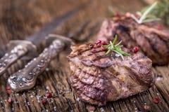 Зажаренный стейк говядины с розмариновым маслом, солью и перцем на старой разделочной доске bedroll стоковые изображения rf