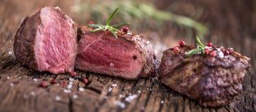 Зажаренный стейк говядины с розмариновым маслом, солью и перцем на старой разделочной доске bedroll стоковые фотографии rf