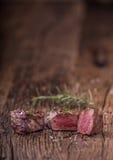 Зажаренный стейк говядины с розмариновым маслом, солью и перцем на старой разделочной доске bedroll стоковые фото