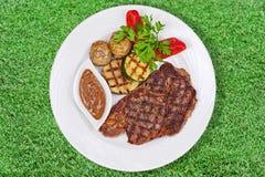 Зажаренный стейк, испеченные картошки и овощи на белой плите на g стоковое изображение rf