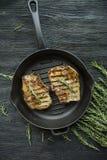 Зажаренный стейк на круглом лотке гриля, гарнированном со специями для мяса, розмаринового масла, зеленых цветов и овощей на темн стоковая фотография rf