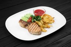 Зажаренный стейк с картошками и овощами на белой плите Стоковая Фотография RF