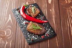 Зажаренный стейк с перцами розмаринового масла и chili на деревянной предпосылке Стоковое фото RF