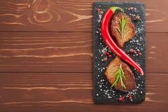 Зажаренный стейк с перцами розмаринового масла и chili на деревянной предпосылке Стоковое Изображение RF