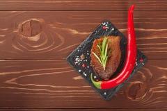 Зажаренный стейк с перцами розмаринового масла и chili на деревянной предпосылке Стоковое Изображение