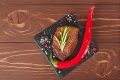 Зажаренный стейк с перцами розмаринового масла и chili на деревянной предпосылке Стоковые Изображения