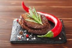 Зажаренный стейк с перцами розмаринового масла и chili на деревянной предпосылке Стоковые Фотографии RF