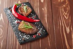 Зажаренный стейк с перцами розмаринового масла и chili на деревянной предпосылке Стоковая Фотография RF
