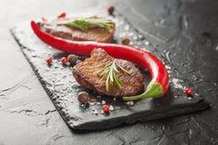 Зажаренный стейк с перцем розмаринового масла и chili на темном камне Стоковые Фото
