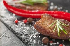 Зажаренный стейк с перцем розмаринового масла и chili на темном камне Стоковая Фотография RF