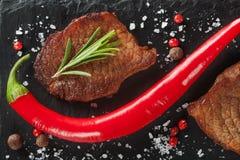 Зажаренный стейк с перцем розмаринового масла и chili на темном камне Стоковое Изображение