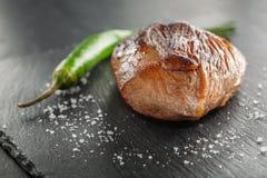 Зажаренный стейк с перцем розмаринового масла и chili на темном камне Стоковые Изображения RF