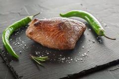 Зажаренный стейк с перцем розмаринового масла и chili на темном камне Стоковое фото RF
