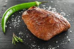 Зажаренный стейк с перцем розмаринового масла и chili на темном камне Стоковые Изображения