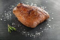 Зажаренный стейк с перцем розмаринового масла и chili на темном камне Стоковая Фотография