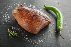 Зажаренный стейк с перцем розмаринового масла и chili на темном камне Стоковое Фото