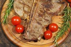 Зажаренный стейк с томатами розмаринового масла, мозоль косточки t, луки и как Стоковые Фотографии RF